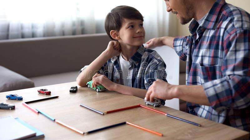 演奏有他微笑的儿子的,父母的照料,统一性的父亲玩具汽车 库存照片