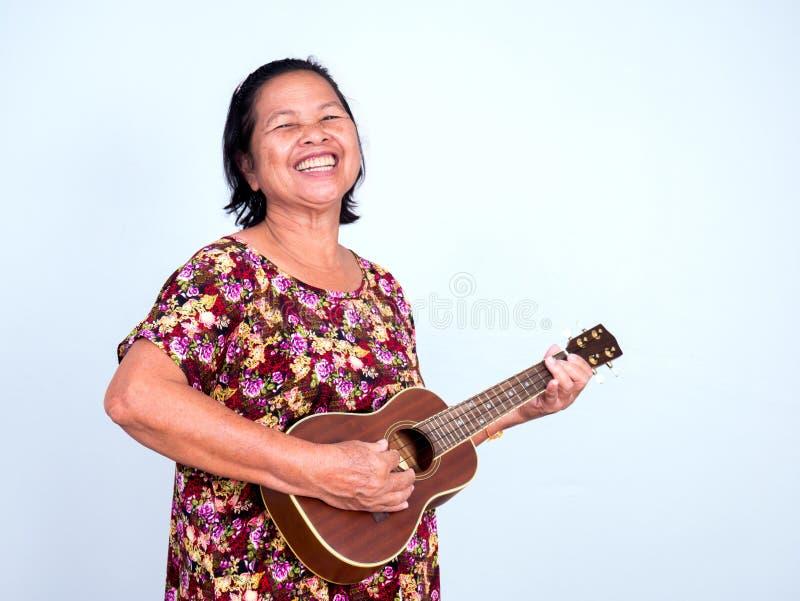 演奏有大微笑的亚裔senoir妇女尤克里里琴 免版税库存图片
