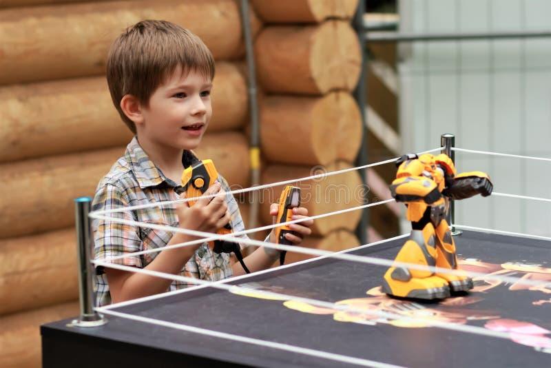 演奏有遥控的男孩争斗战斗的机器人 免版税库存图片
