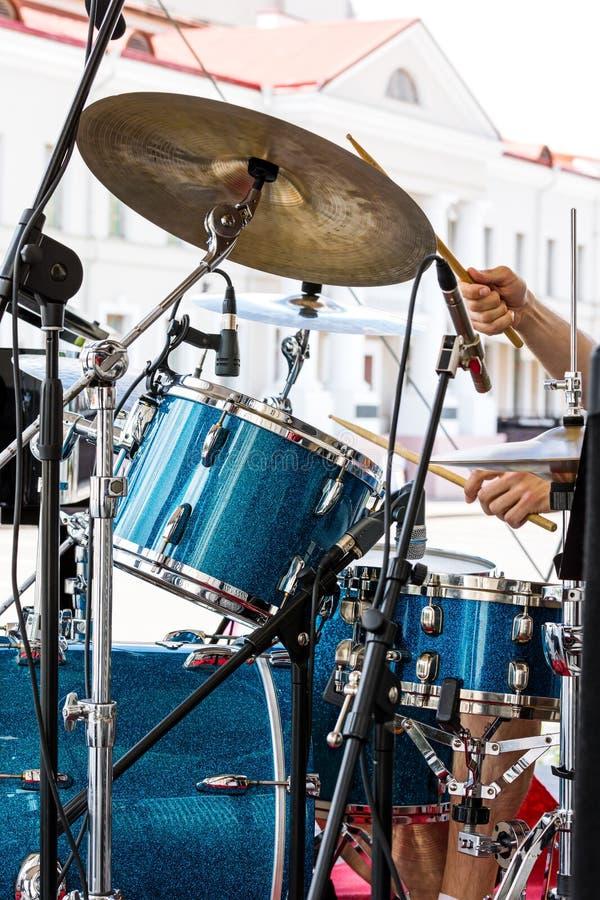 演奏有鼓槌的街道音乐家鼓在他的手上 图库摄影