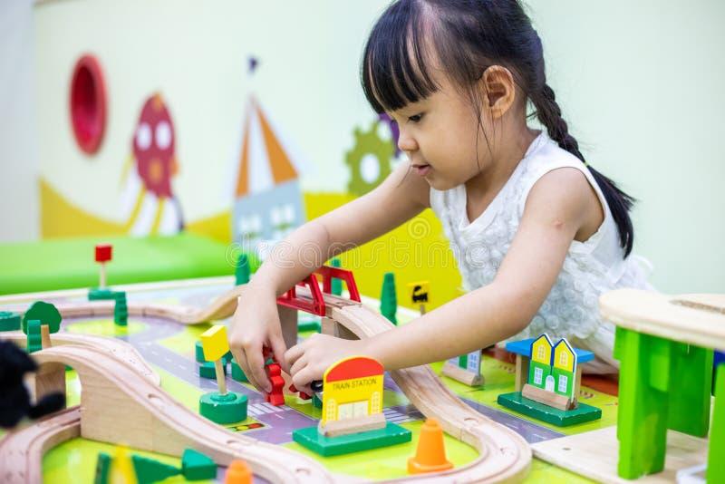 演奏木玩具火车的亚裔中国小女孩 免版税库存图片