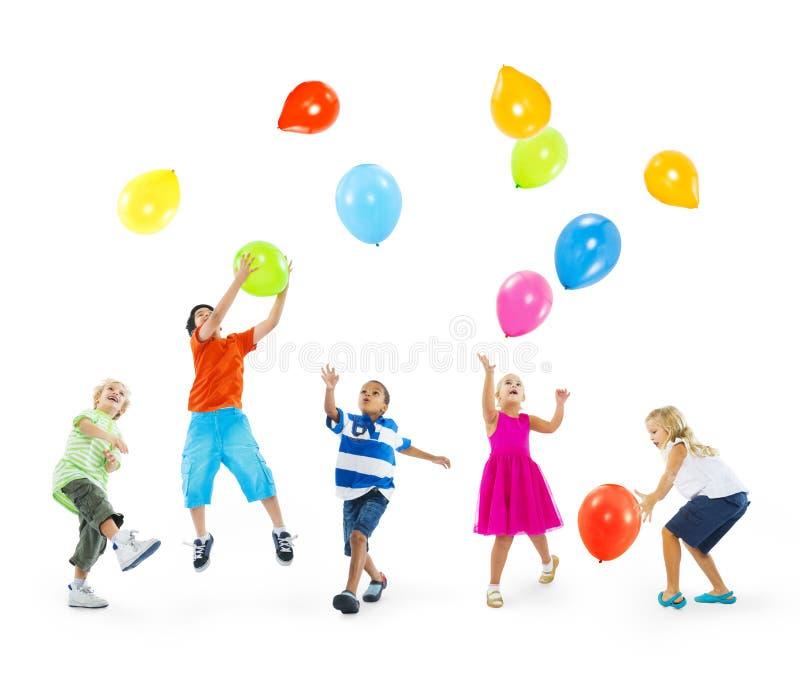演奏气球的愉快的不同种族的孩子 库存图片