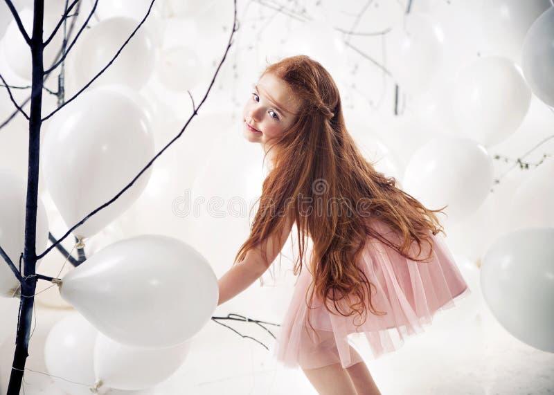演奏气球的逗人喜爱的小女孩 免版税库存图片