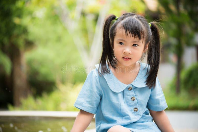 演奏水的愉快的小女孩在五颜六色的庭院里在热的夏天 库存照片