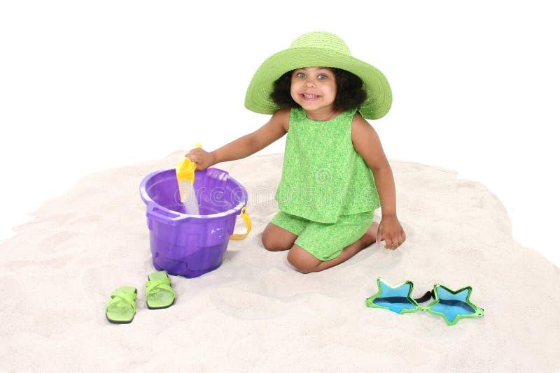 演奏沙子坐的年轻人的美丽的女孩 免版税库存图片
