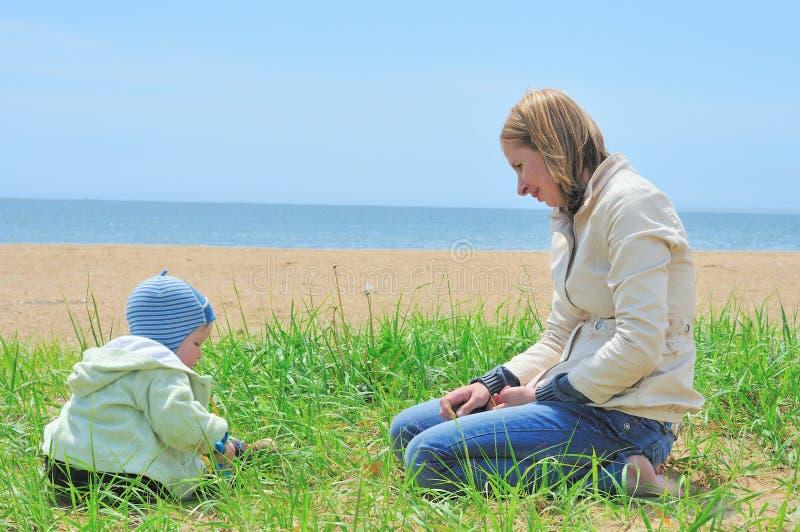 演奏沙子的小母亲 免版税图库摄影