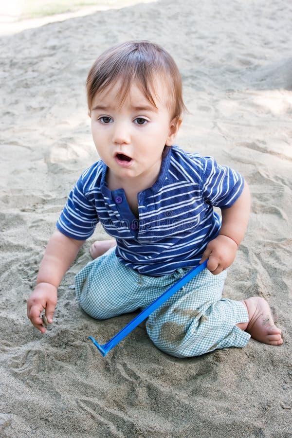 演奏沙子的逗人喜爱的孩子 免版税库存图片