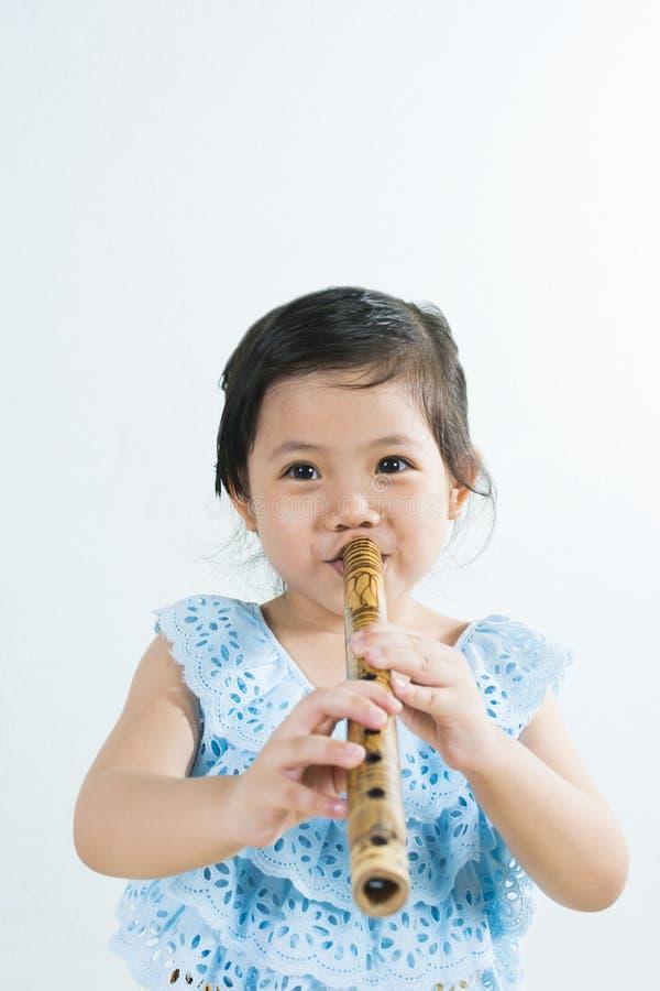 演奏泰国竹子F的传统礼服的泰国矮小的逗人喜爱的女孩 免版税库存图片