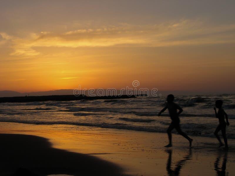 演奏海海滩日落的孩子 跑在海滩的两个男孩在日落时间 免版税库存图片
