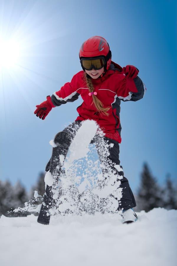演奏滑雪者雪年轻人的女孩 免版税库存照片