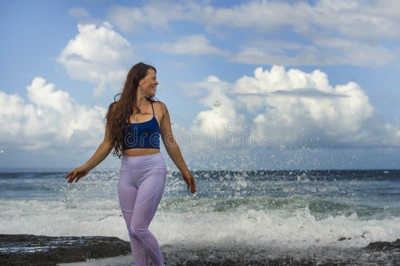演奏激动的传播的胳膊的年轻愉快和可爱的红色头发妇女感觉自由和轻松得到湿由海波浪 免版税库存照片