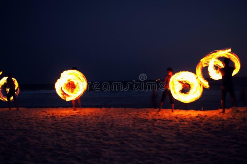 演奏烟花的高技艺人通过转动与燃料油和火,圈子的木杆作为火光环在海滩的沿海洋 免版税库存照片