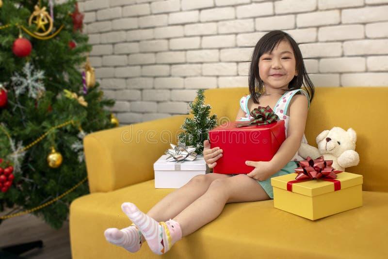 演奏玩偶的女孩 X-mas和假日概念 有礼物盒的愉快的儿童女孩 女孩在圣诞节盖帽手上出席包裹与 免版税图库摄影