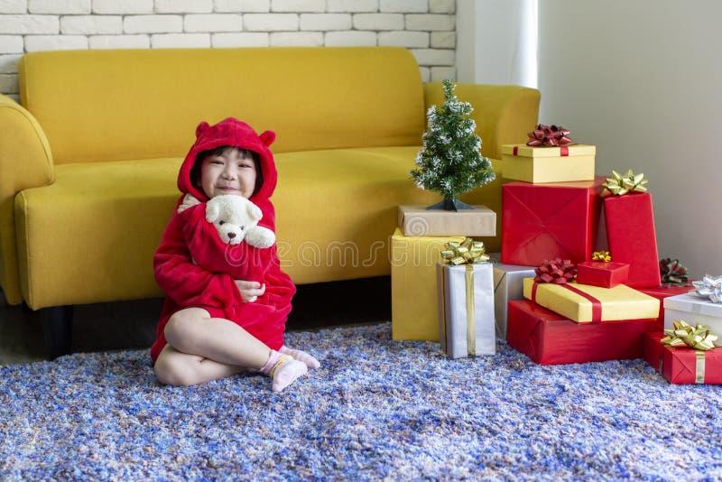 演奏玩偶的女孩 X-mas和假日概念 有礼物盒的愉快的儿童女孩 女孩在圣诞节盖帽手上出席包裹与 免版税库存照片