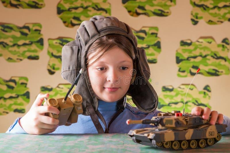 演奏玩具军事坦克的女孩 图库摄影