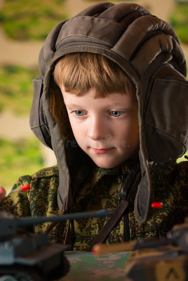 演奏玩具军事坦克的男孩 图库摄影
