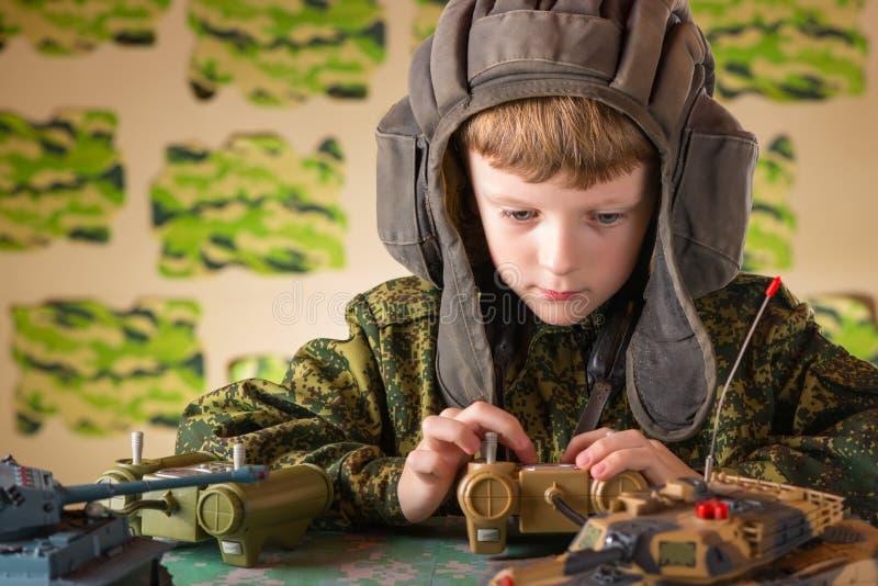演奏玩具军事坦克的男孩 免版税图库摄影