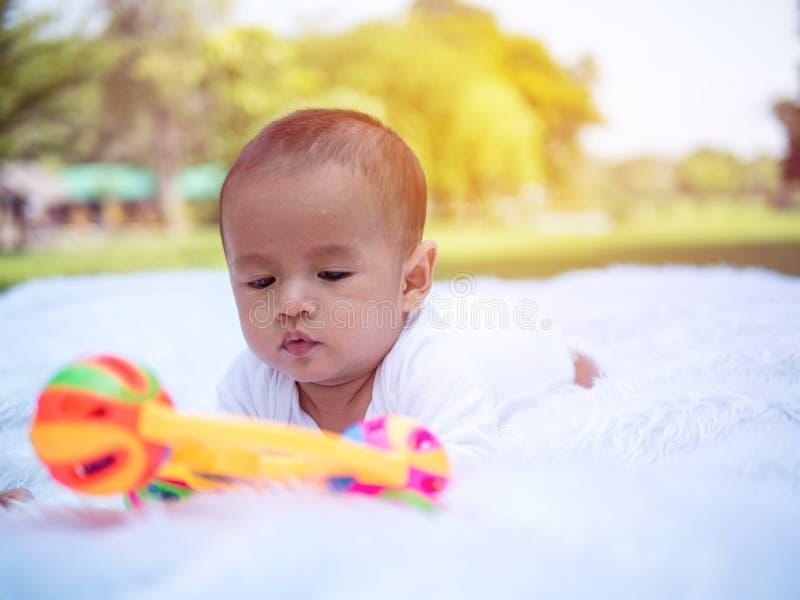 演奏玩具在夏天在公园,婴儿轻便小床的玩具的新生儿 免版税库存图片