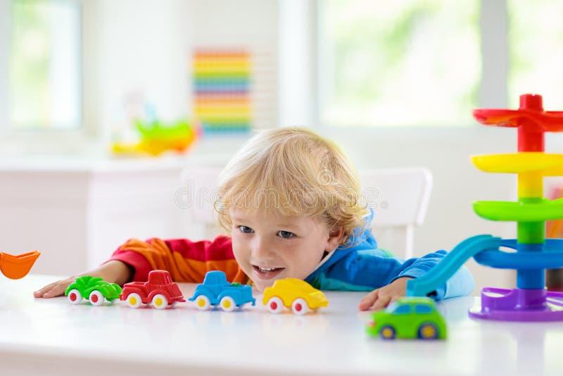 演奏玩具汽车的男孩 r 孩子和汽车 免版税图库摄影