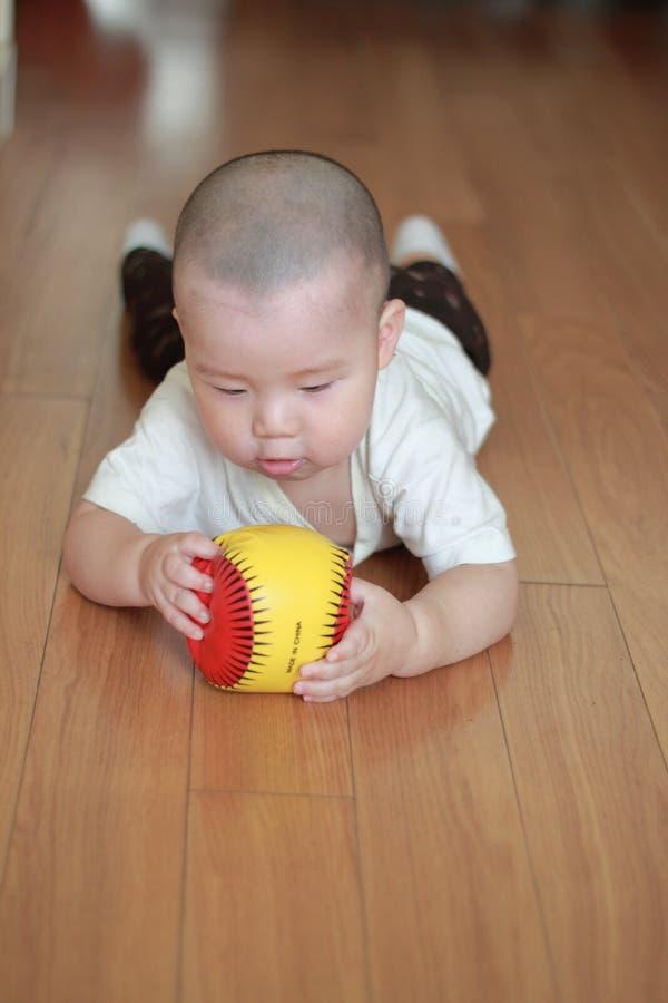 演奏玩具的婴孩爬行的楼层 库存图片