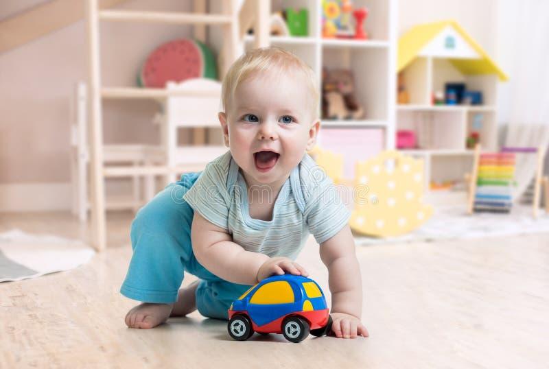 演奏玩具的滑稽的男婴在托儿所 免版税库存照片
