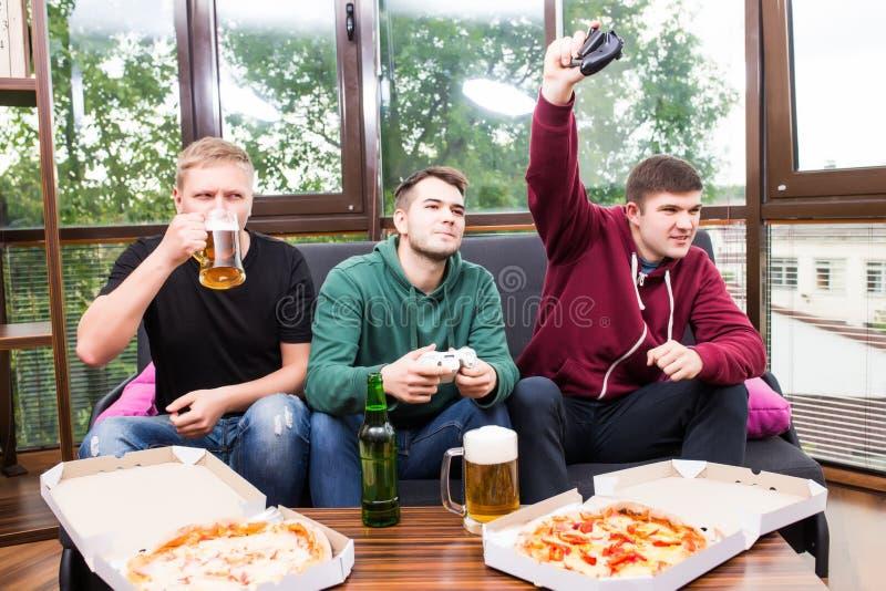 演奏电子游戏,饮料啤酒的男性朋友和在家获得乐趣 图库摄影
