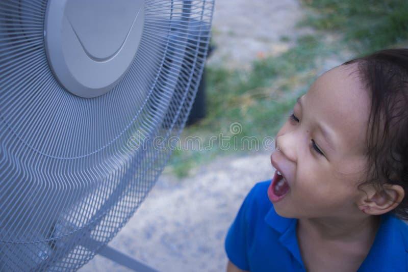 演奏电风扇和享用在夏季的孩子凉风 免版税库存照片