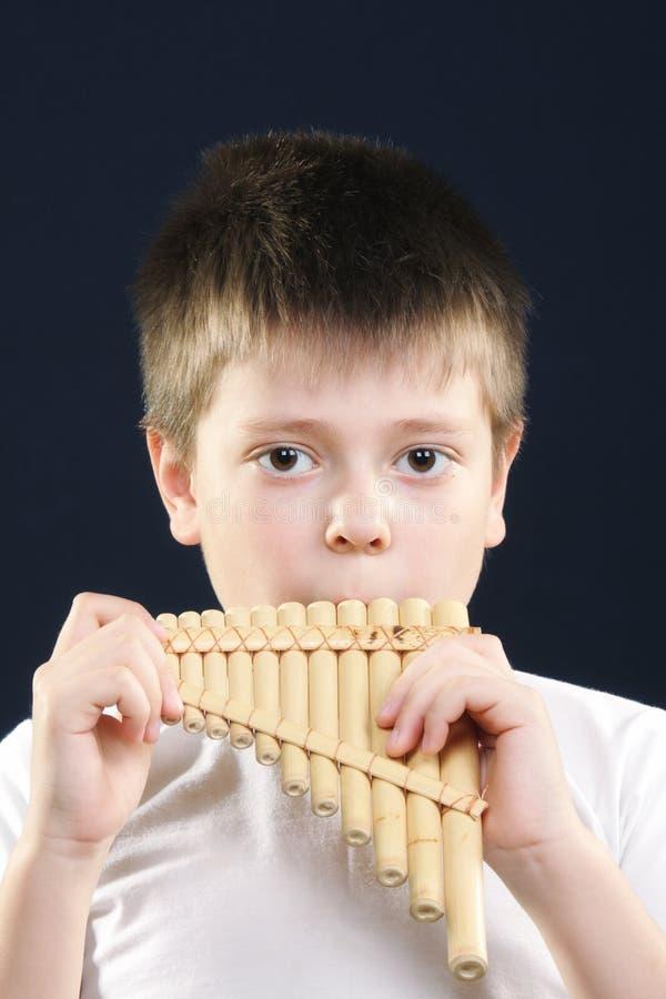 演奏白色的男孩panflute 免版税库存照片