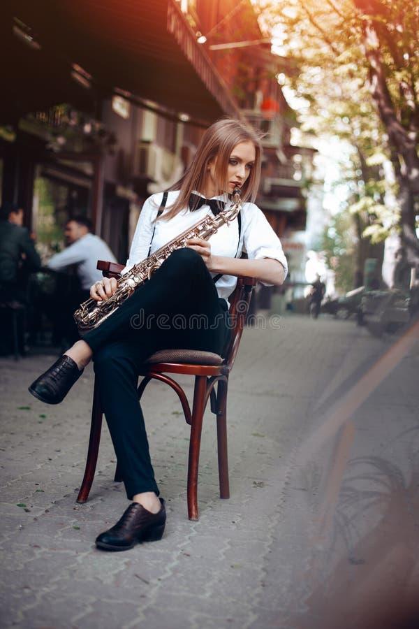 演奏白色衬衣的年轻可爱的女孩有坐在caffe附近的萨克斯管的购物-室外在sity 有萨克斯管的性感的少妇 免版税库存照片