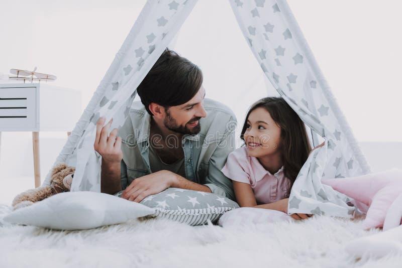 演奏的小屋逗人喜爱的年轻女儿与英俊的爸爸 库存照片