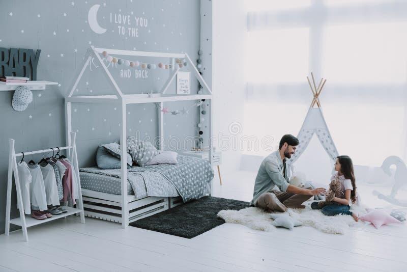 演奏的小屋逗人喜爱的年轻女儿与英俊的爸爸 免版税库存图片