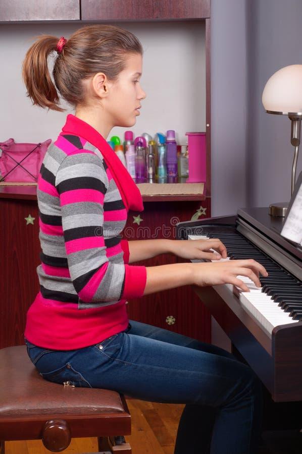 演奏相当少年的女孩钢琴 库存图片