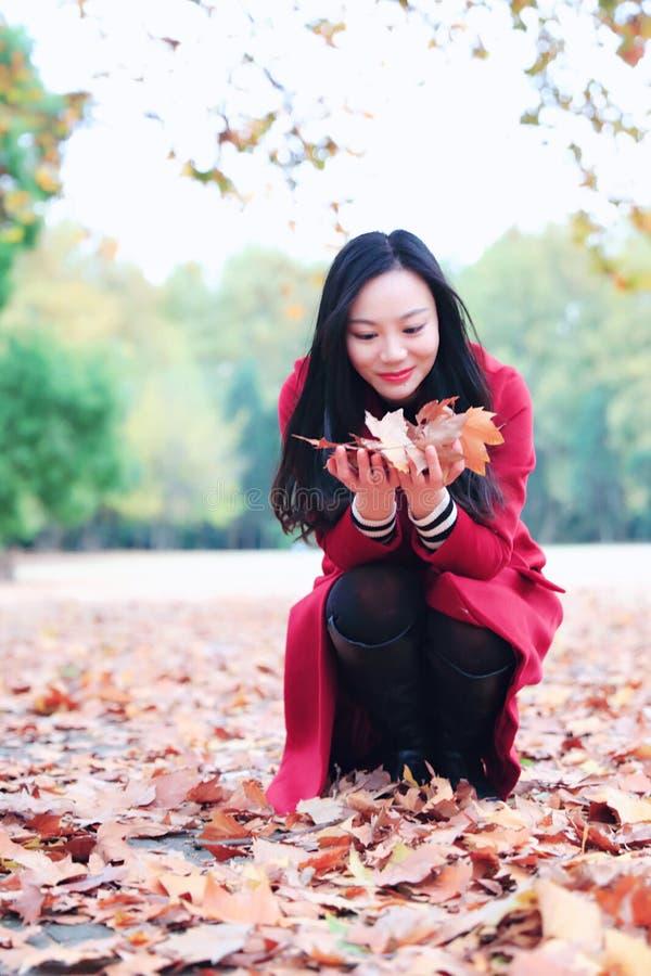 演奏秋天叶子的女孩 免版税图库摄影