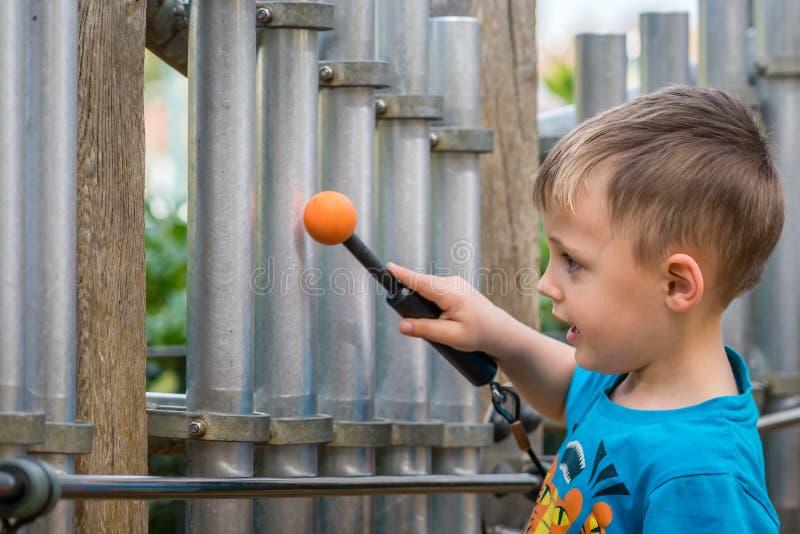 演奏筒形响铃的小男孩 免版税库存照片