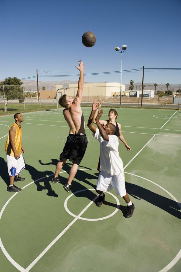 演奏篮子球的多种族小组 免版税库存图片