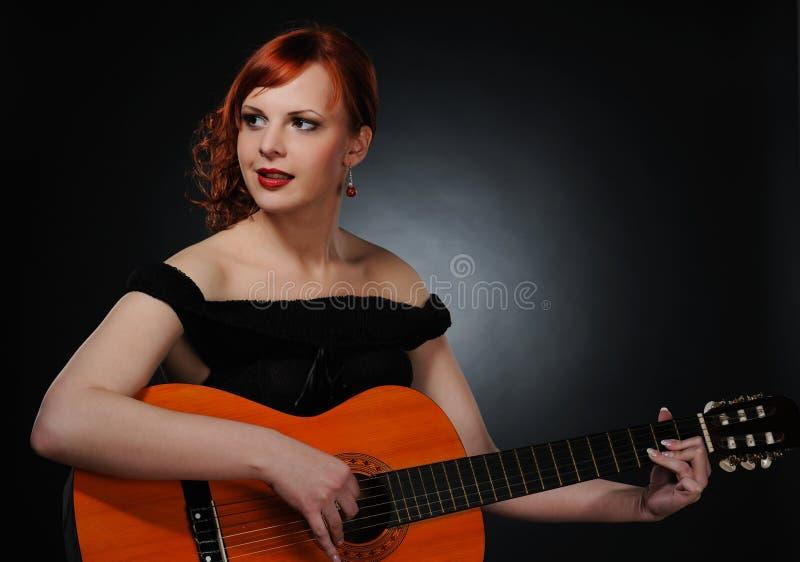 演奏红头发人妇女的美丽的吉他 免版税图库摄影