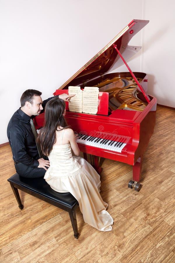 演奏红色的夫妇钢琴 免版税图库摄影