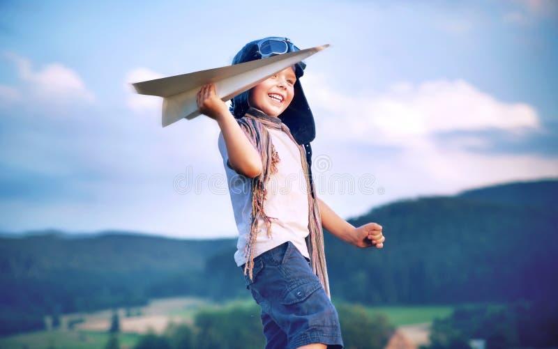 演奏纸飞机的快乐的小男孩 免版税库存照片
