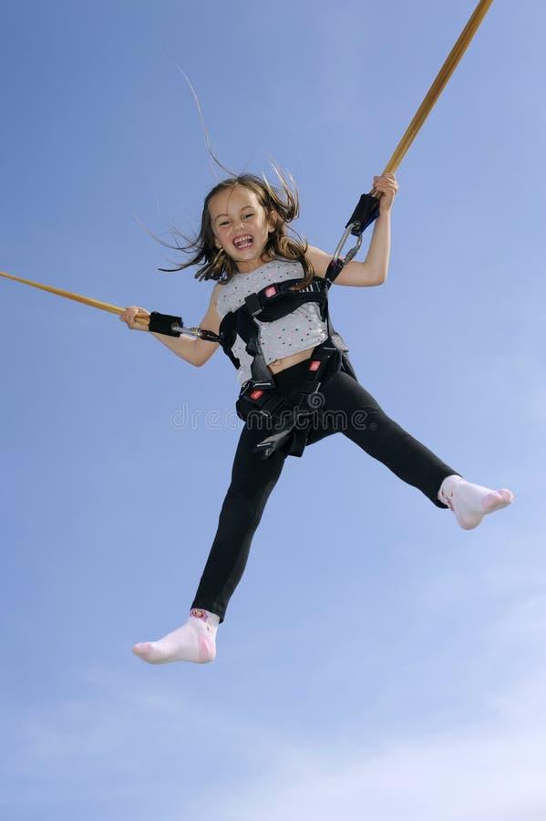 演奏绷床年轻人的橡皮筋女孩 免版税图库摄影