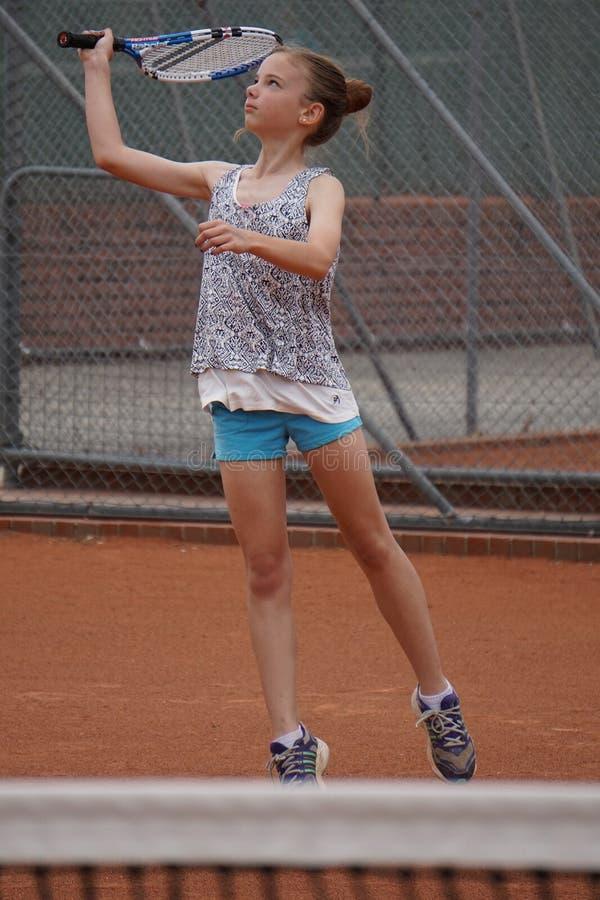 演奏网球年轻人的女孩 免版税库存照片