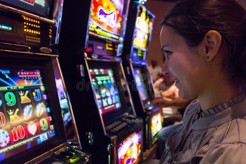 演奏老虎机的幸运妇女在赌博娱乐场 免版税库存照片