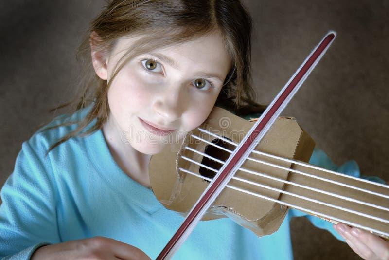 演奏自创玩具Violyn的小女孩 免版税库存图片