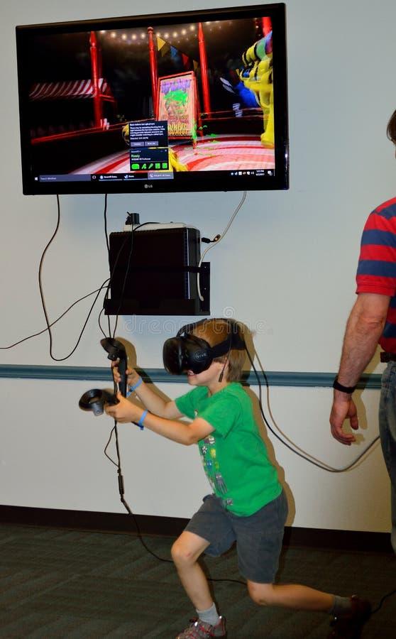 演奏虚拟现实的男孩-屏幕耳机和控制器 库存照片