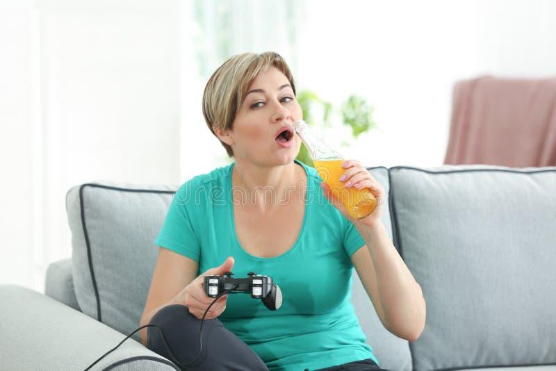 演奏计算机游戏和喝苏打的成熟妇女,当在家时坐沙发 免版税库存照片