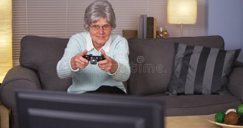 演奏计算机游戏的年长妇女 图库摄影