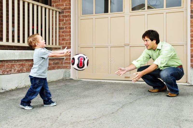 演奏足球儿子的父亲 免版税库存照片