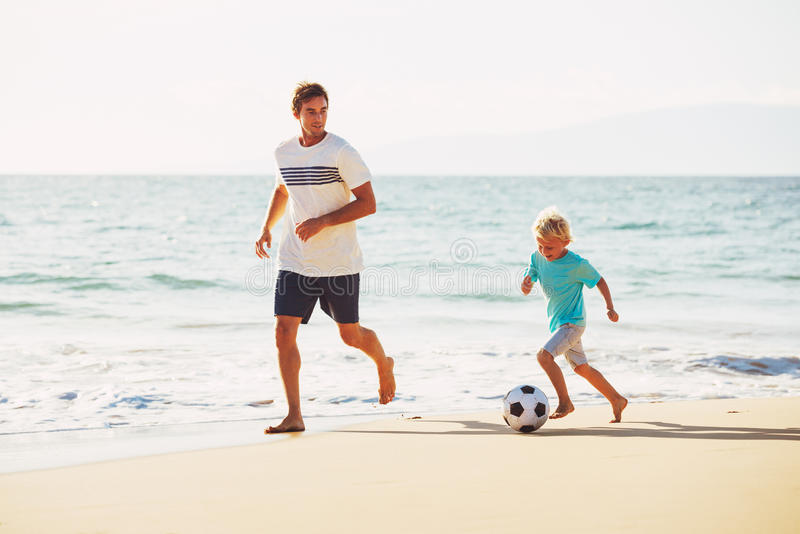 演奏足球儿子的父亲 免版税库存图片