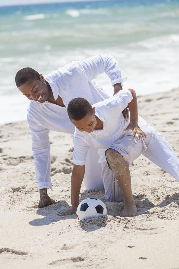 演奏足球海滩的非洲裔美国人的父亲儿子 免版税库存照片