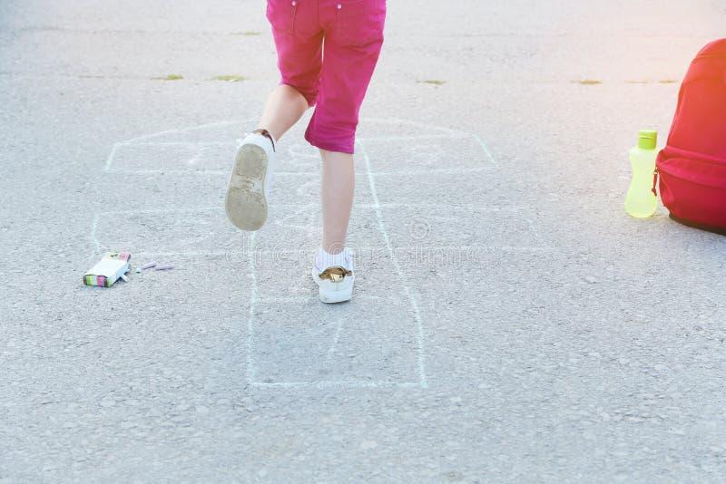 演奏跳房子画与在沥青的五颜六色的白垩小学外,教育概念的美丽的白肤金发的女小学生 库存图片