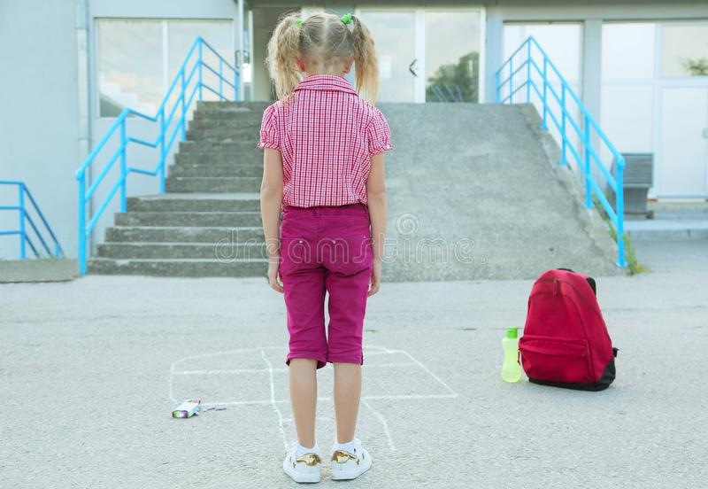 演奏跳房子画与在沥青的五颜六色的白垩小学外,教育概念的美丽的白肤金发的女小学生 免版税库存图片